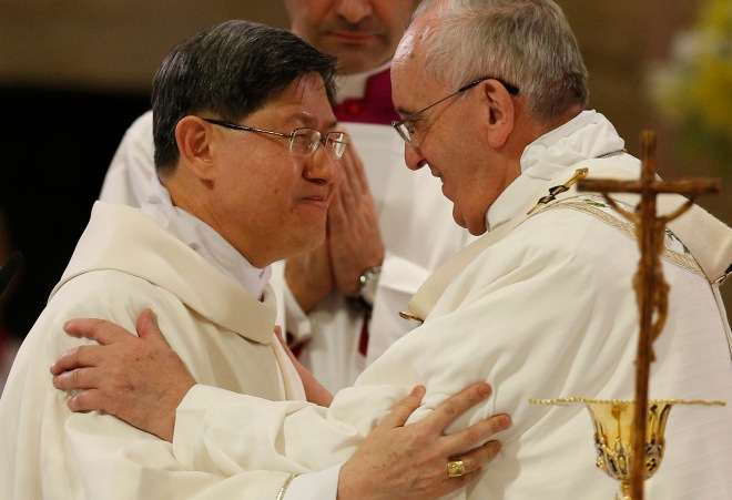 Pope Francis greets Cardinal Luis Antonio Tagle of Manila at the sign of peace at cathedral in Manila, Philippines